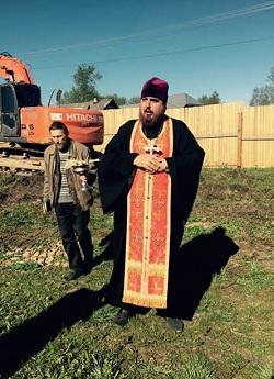 Отец Михаил освящает площадку для строительства храма